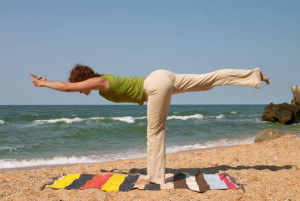 girl doing virabhadrasana yoga pose at sea coast